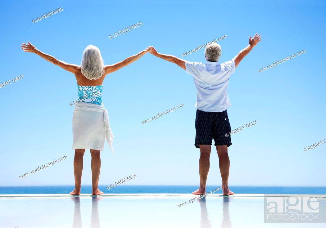 Stock Photo: Senior couple standing at edge of infinity pool with arms outstretched.