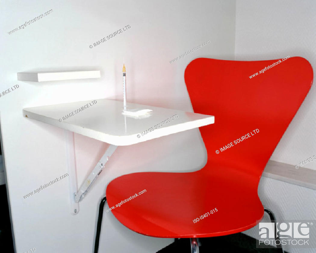 Stock Photo: Red chair and syringe.