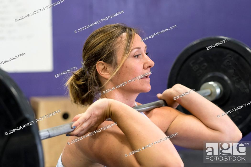 Stock Photo: Fit young woman lifting weights at a crossfit gym.