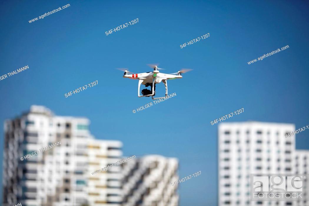 Imagen: Drohne fliegt in blauem Himmel in der Nähe von Hochhäusern.