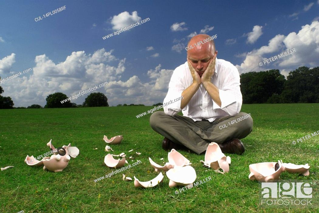 Stock Photo: man and smashed piggy banks.