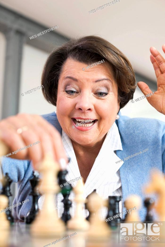Stock Photo: Germany, Leipzig, Senior woman playing chess game.