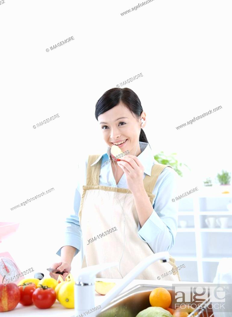 Stock Photo: Young woman eating apple with knife in hand, fresh fruits around.
