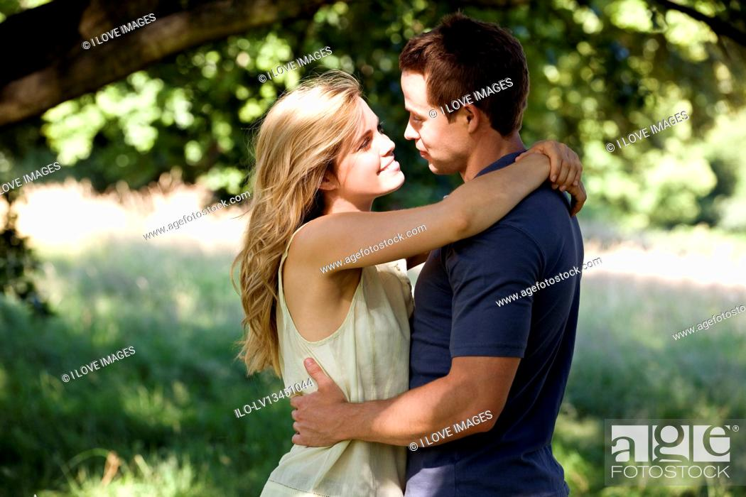 Stock Photo: A young couple standing beneath a tree, embracing.