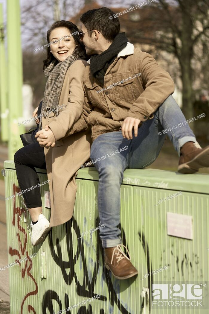 Stock Photo: young teenage couple sitting on electricity distribution board in city, in Cottbus, Brandenburg, Germany.