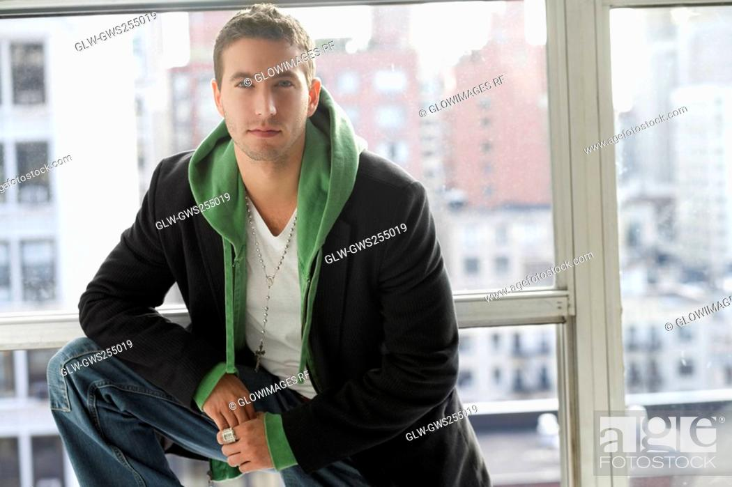 Stock Photo: Portrait of a young man standing with his hand on his knee.