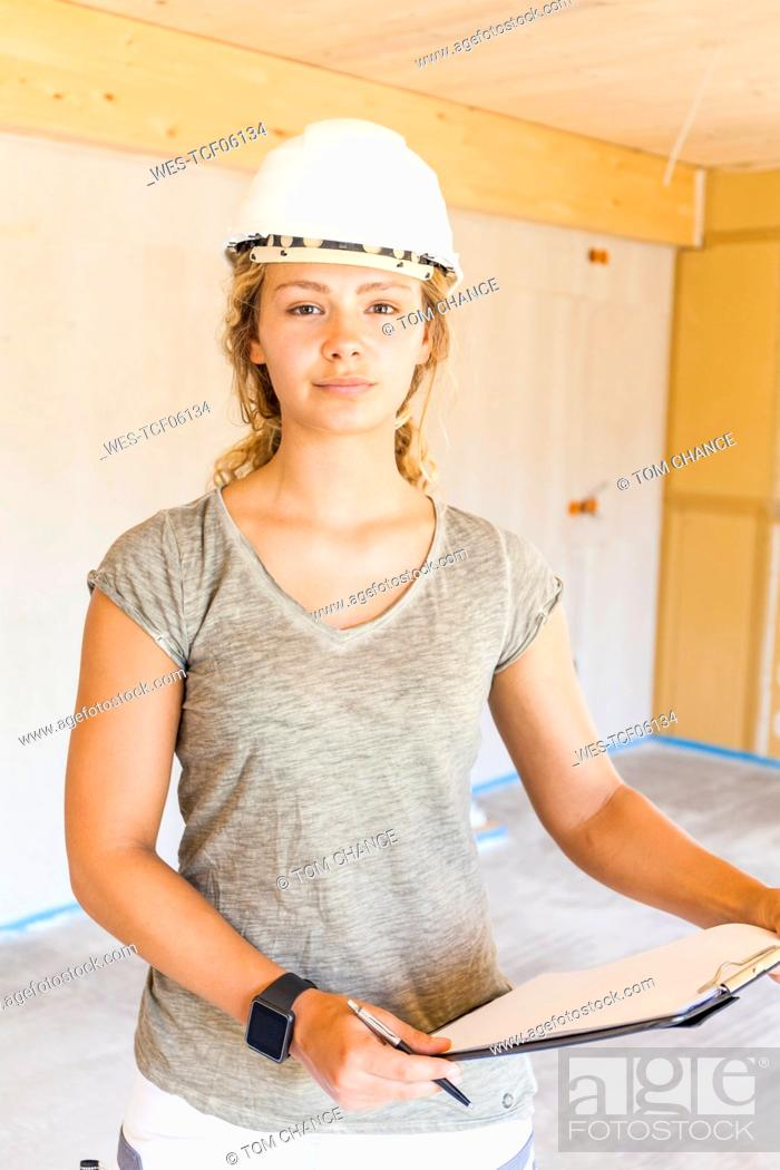 Stock Photo: Portrait of a confident young woman in a new wooden house.