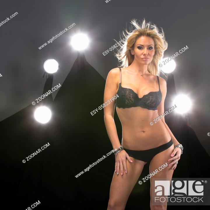 Stock Photo: An attractive blonde lingerie model poses in a studio environment with lights in the background.A blonde attractive lingerie model poses in a studio environment.