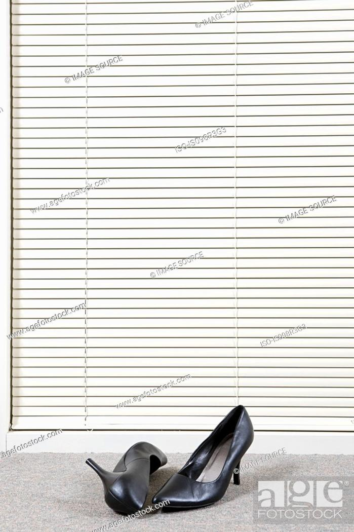 Stock Photo: Pair of high heeled shoes in front of venetian blinds.