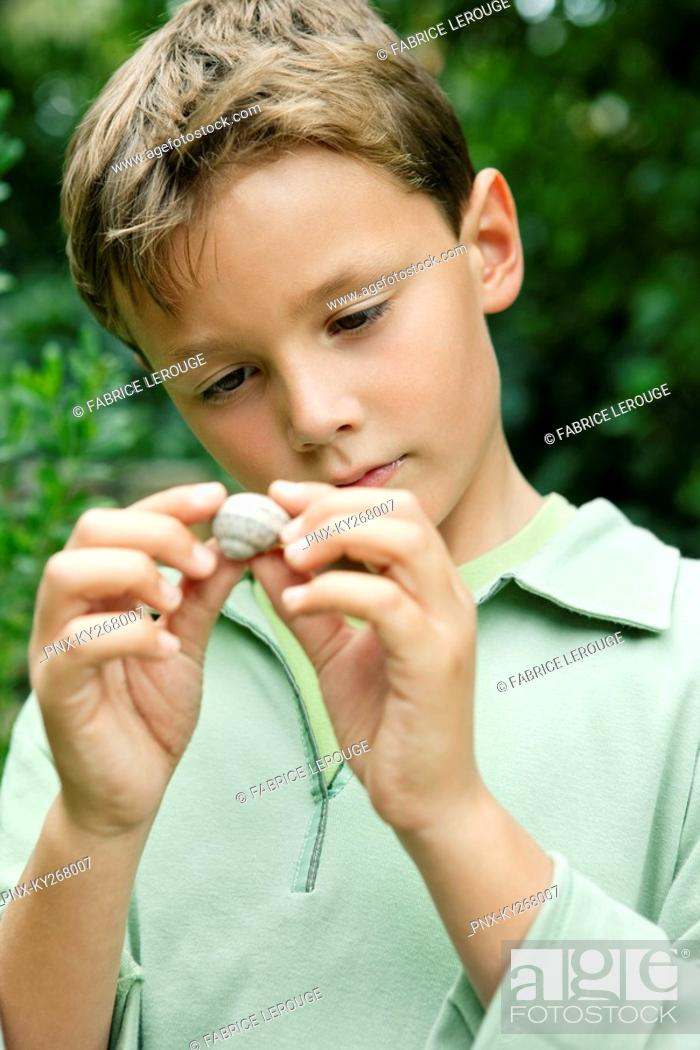 Stock Photo: Boy holding a seashell.