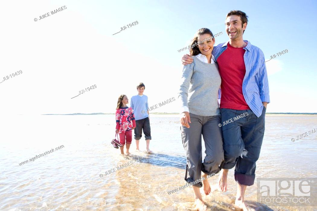 Stock Photo: Parents with children walking on beach.