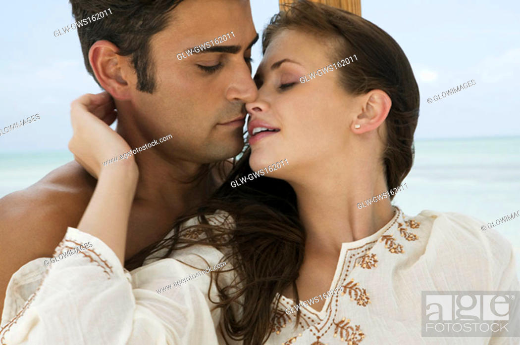 Stock Photo: Close-up of a young woman and a mid adult man embracing each other.