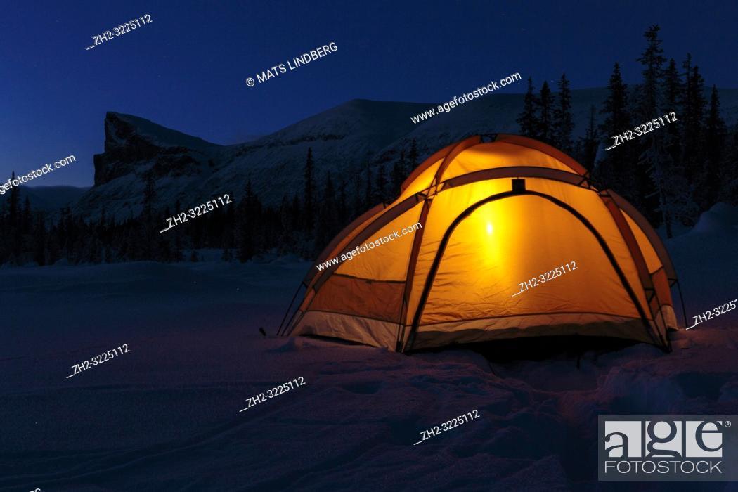 Imagen: Camping in winter season at night, lantern shining in the tent, Mount Skerfe and Sarek national park in background, Jokkmokk county, Sarek national park.