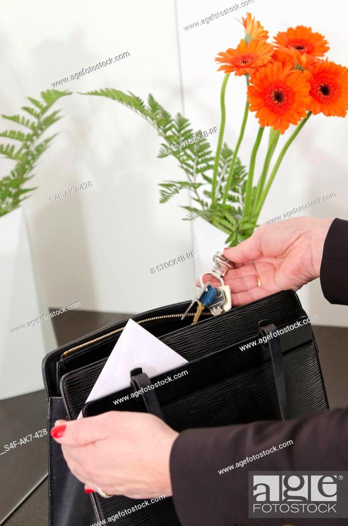 Stock Photo: Woman taking key ring from handbag.