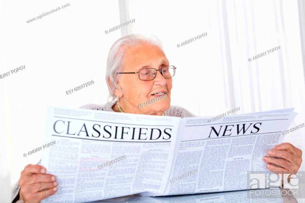 Stock Photo: Happy Senior Woman Reading Newspaper On Desk At Home.
