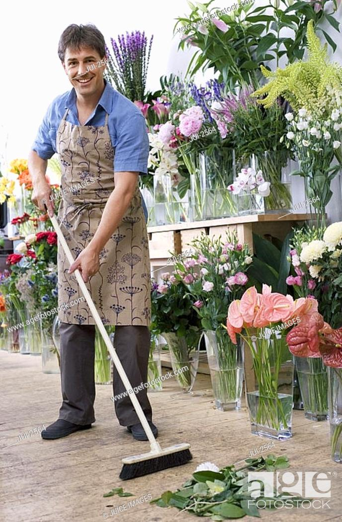 Stock Photo: Male florist in apron standing in flower shop, sweeping floor with broom, smiling, portrait.