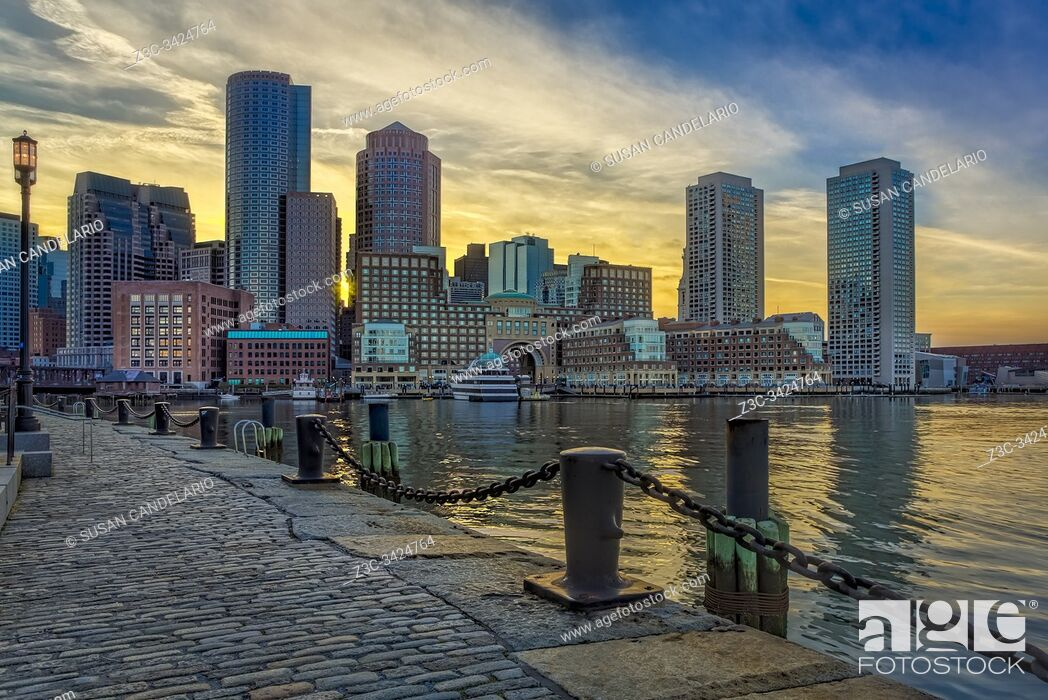 Stock Photo: A view during sunset to the Boston Harbor with the Boston Financial District's dramatic skyline and colorful sky.