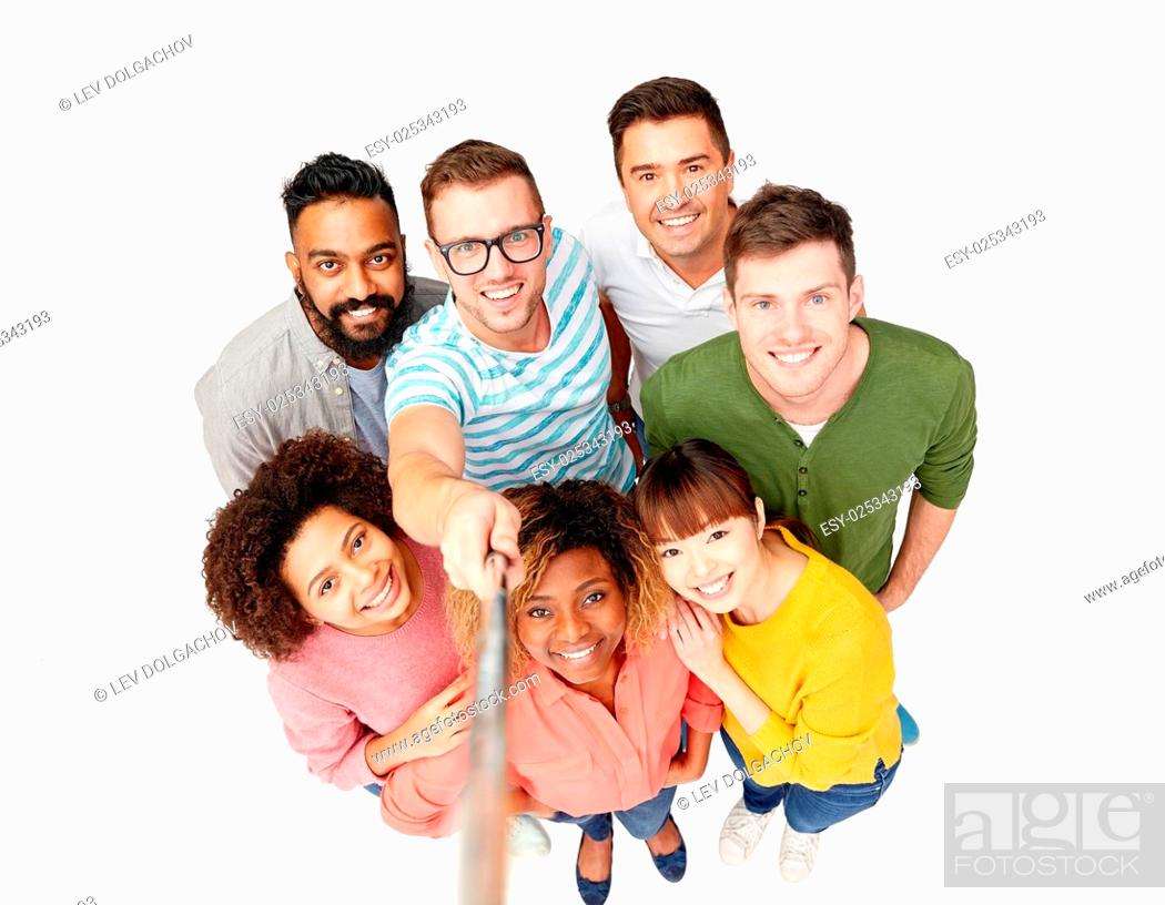 Stock Photo: diversity, race, ethnicity, technology and people concept - international group of happy smiling men and women taking picture by selfie stick over white.