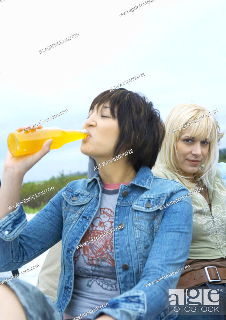 Stock Photo: Young woman drinking orange soda.