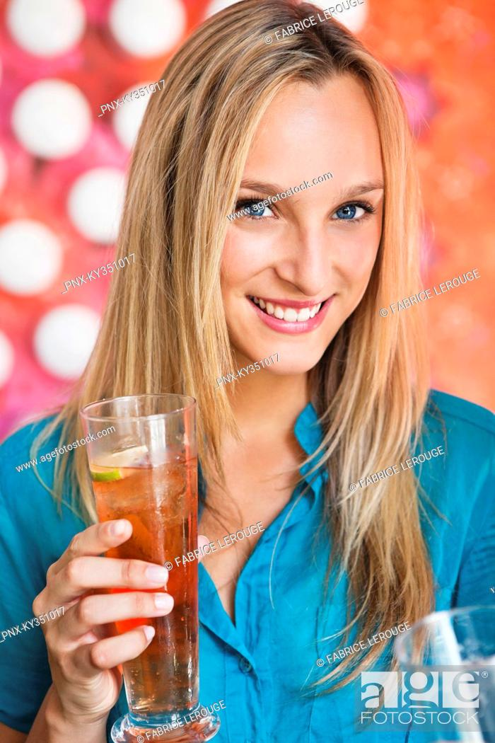 Stock Photo: Portrait of a beautiful woman having ice tea in a bar and smiling.