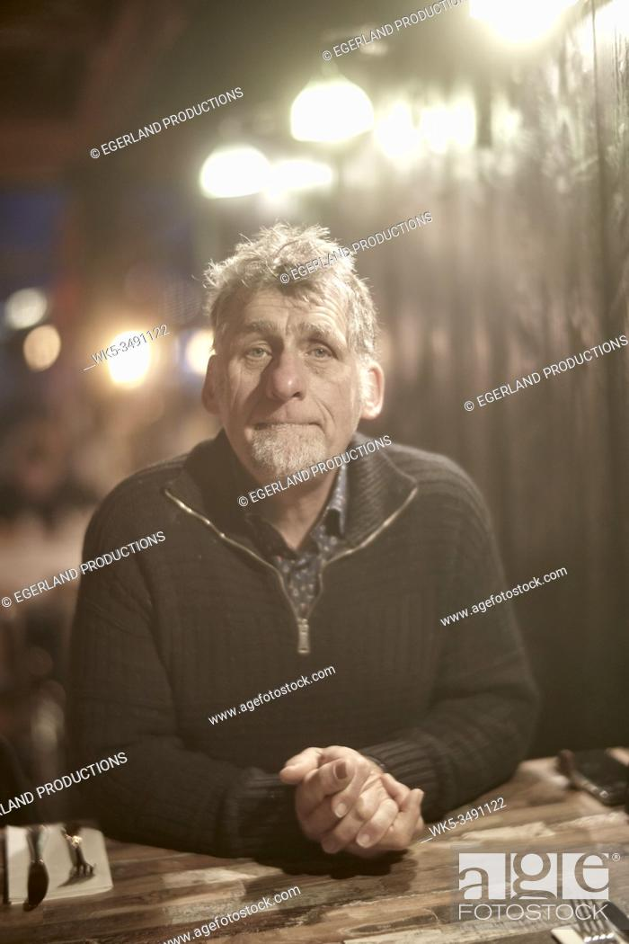 Stock Photo: Friesian senior man sitting at table in restaurant.