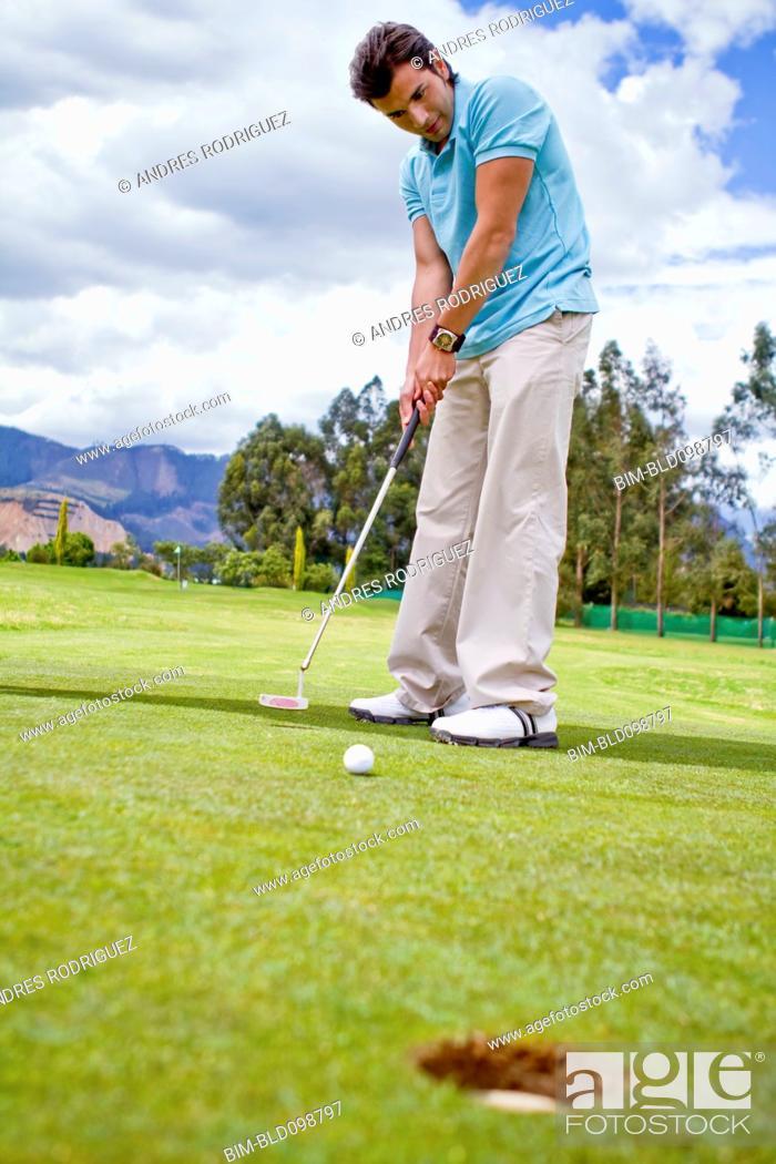 Stock Photo: Hispanic man putting golf ball.