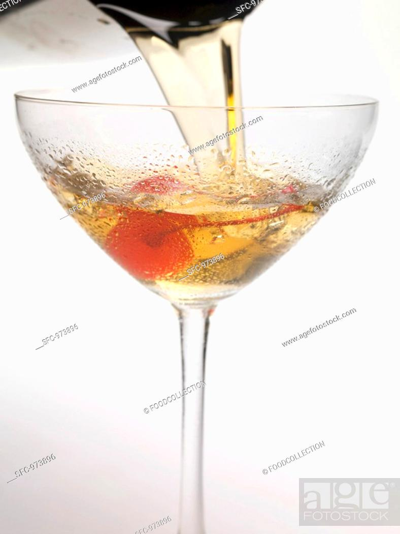 Stock Photo: Pouring Manhattan out of cocktail shaker into glass.