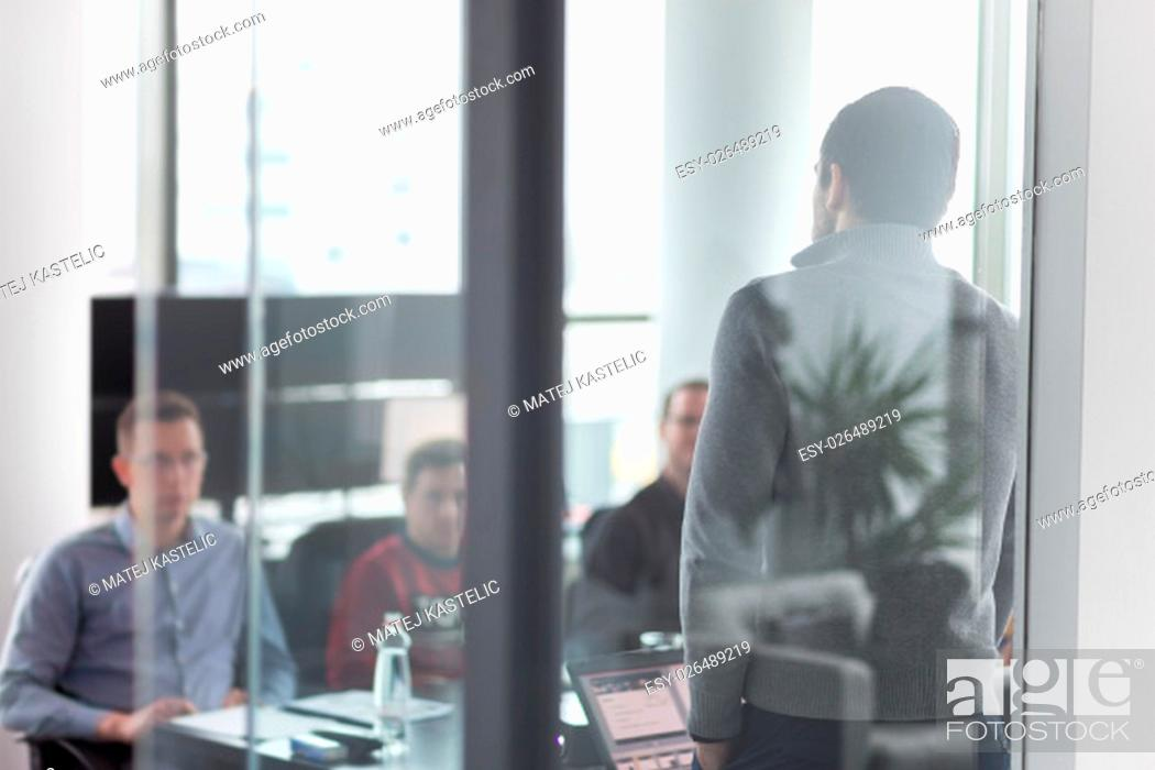 Stock Photo: Businessman making a presentation at office. Business team leader delivering a presentation to his colleagues during meeting or in-house business training.
