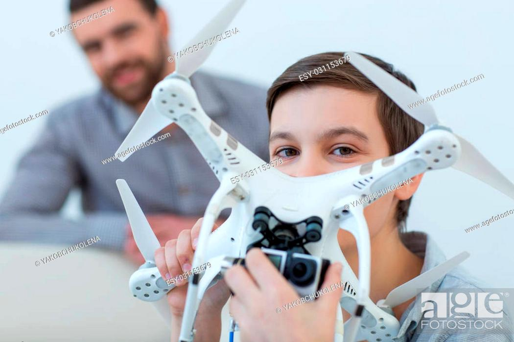 Stock Photo: Look at this camera and smile. Cheerful boy is holding a quadrocopter and adjusting the camera with joy. His father is standing behind him and smiling.