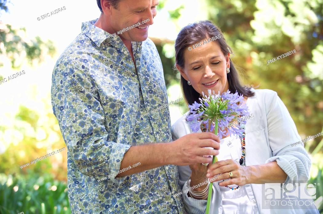 Stock Photo: Man giving flower to his mother and smiling.