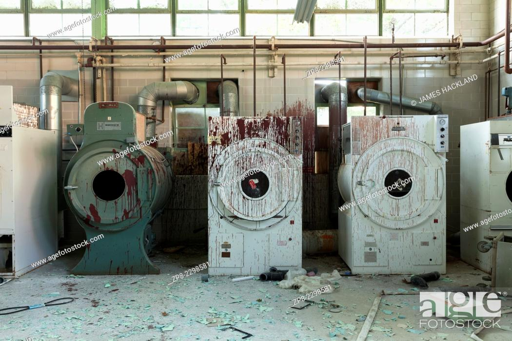 Stock Photo: Industrial washers and dryers covered in red paint in an abandoned hospital. Ontario, Canada.