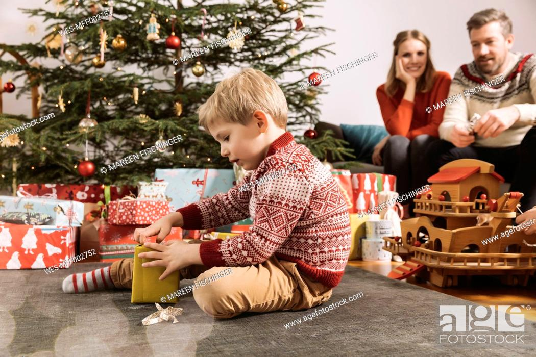 Stock Photo: Little boy opening Christmas gift with parents watching in background.