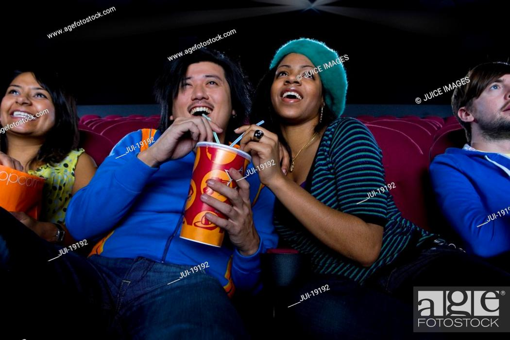 Stock Photo: Couple sharing drink in cinema, smiling, low angle view.