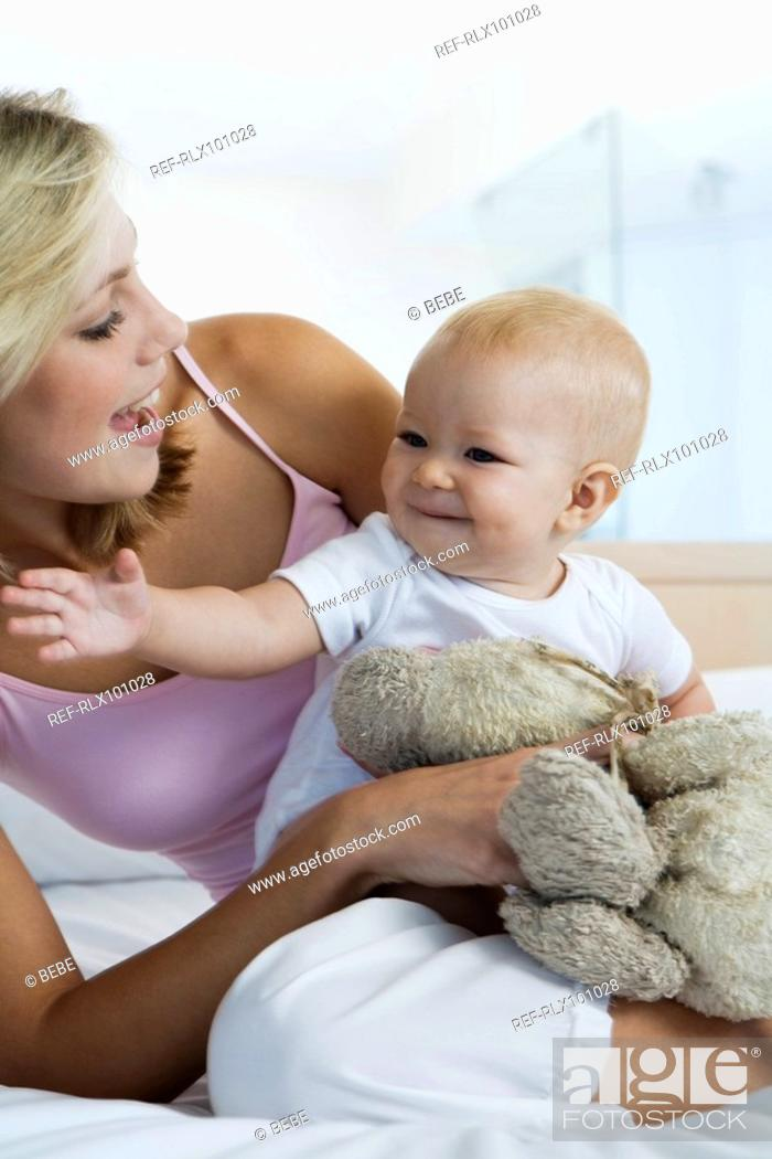 Stock Photo: Young mother sitting with baby 6-12 months in bedroom.