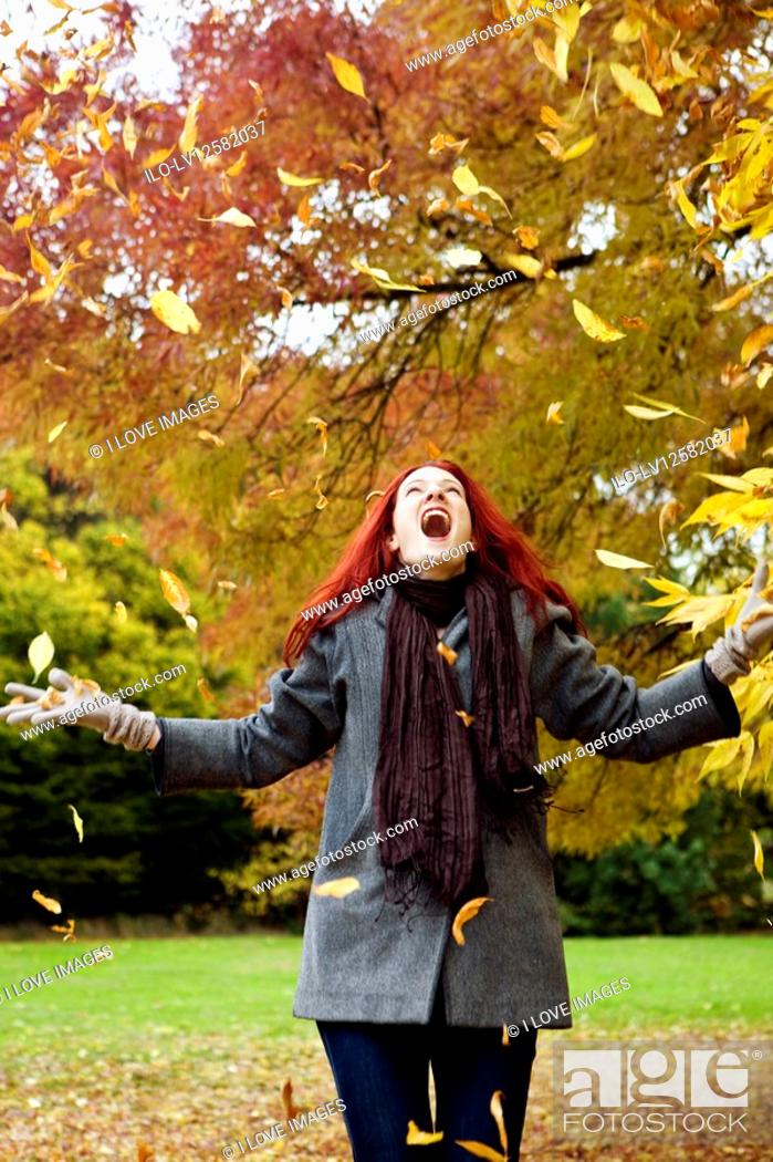 Stock Photo: A young woman throwing autumn leaves in the air.