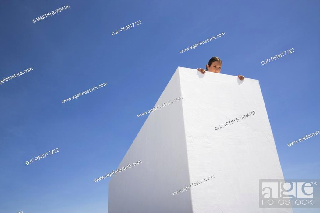 Stock Photo: Woman looking over edge of roof.