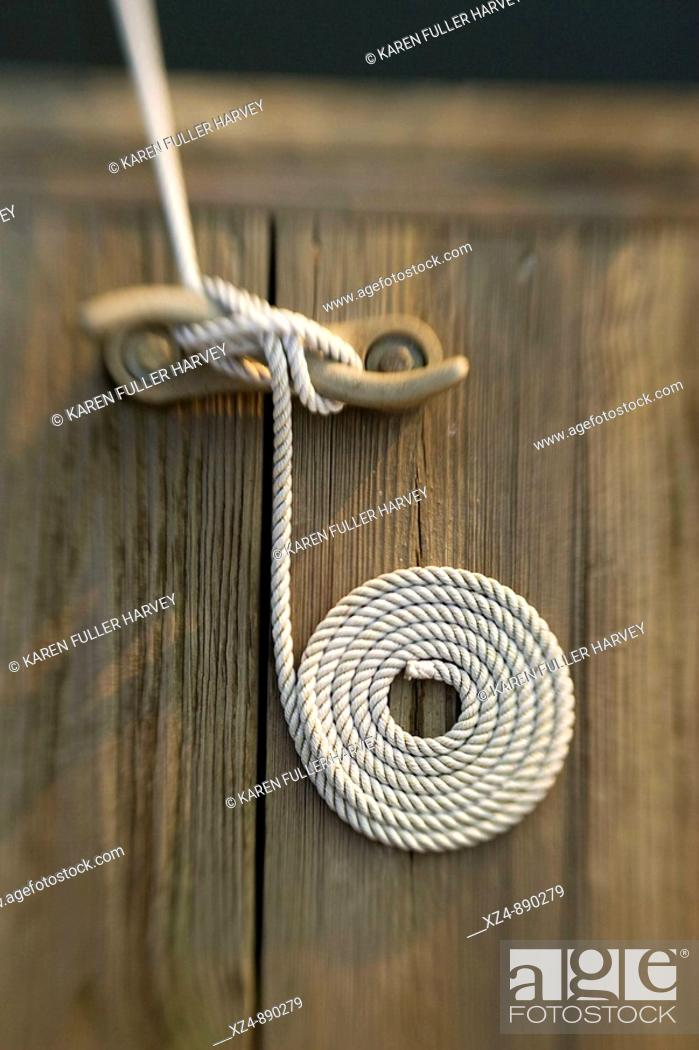 Stock Photo: carefully cleated line from boat on dock is neatly presented.
