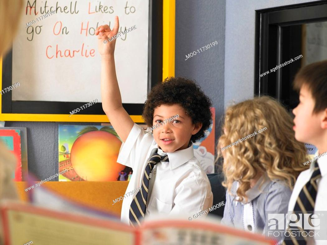 Stock Photo: Elementary schoolboy raising hand in classroom.