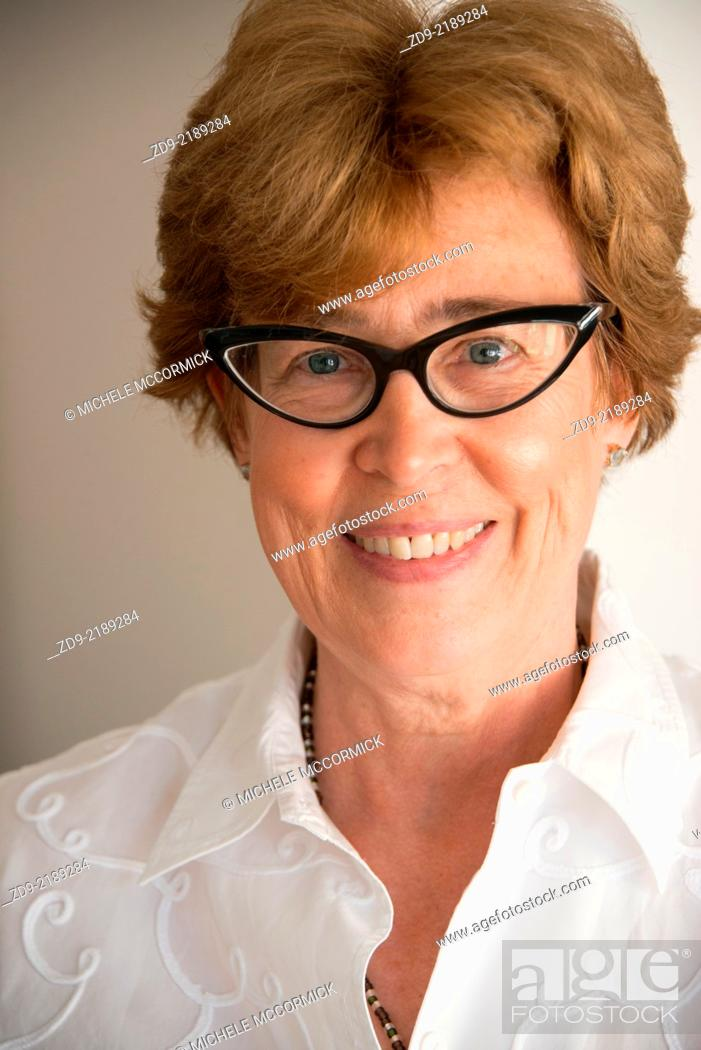 Stock Photo: A middle aged woman smiles through her cat's-eye glasses.