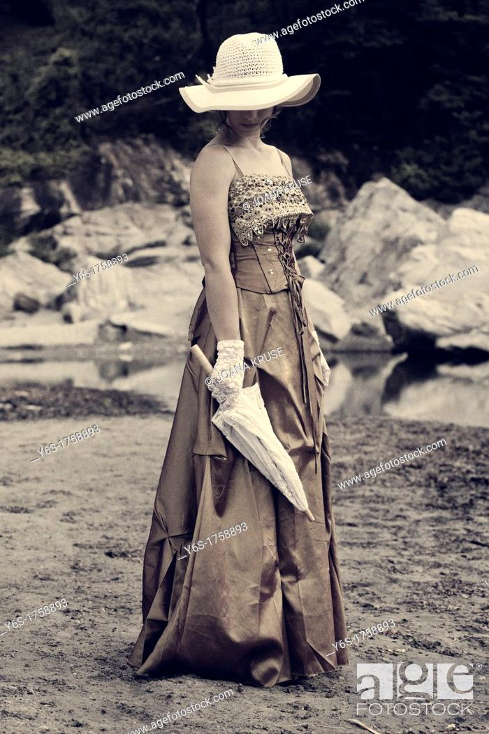 Stock Photo: a young woman in a romantic period dress standing on the shore of a lake.