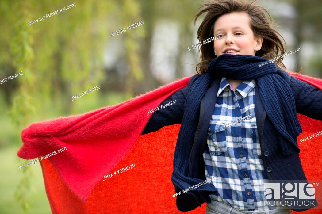 Stock Photo: Girl holding a blanket with her arm outstretched.