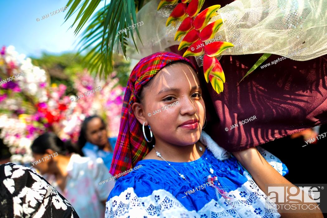 Stock Photo: Salvadoran girls carry an altar with a statue of Virgin Mary during the procession of the Flower & Palm Festival in Panchimalco, El Salvador.