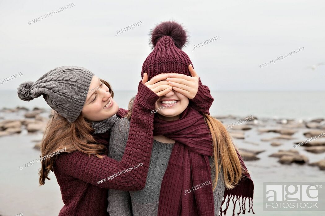 Stock Photo: Two friends playing on the beach wearing knit hats and scarves, Woodbine Beach; Toronto, Ontario, Canada.