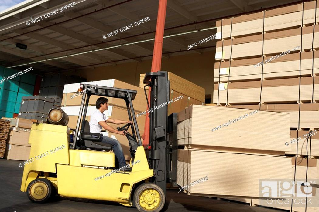 Stock Photo: Side view of male worker operating forklift vehicle.