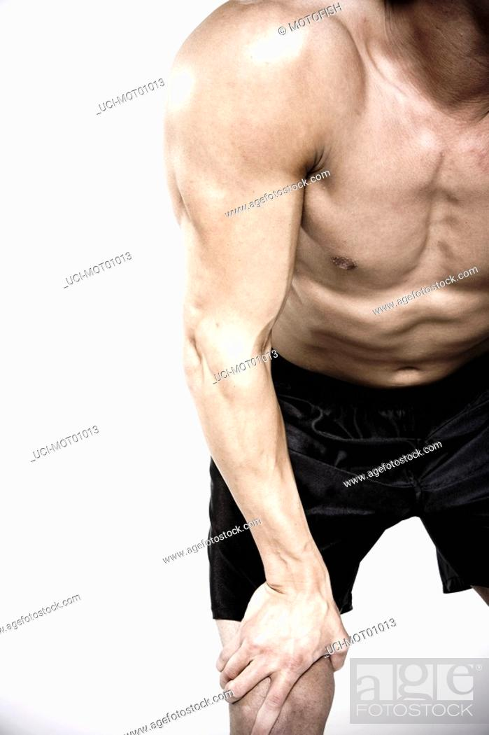 Stock Photo: Bare-chested man leaning arm on knee.