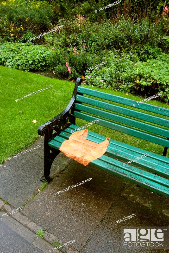 Stock Photo: Park bench in the rain with orange plastic bag placed on seat.
