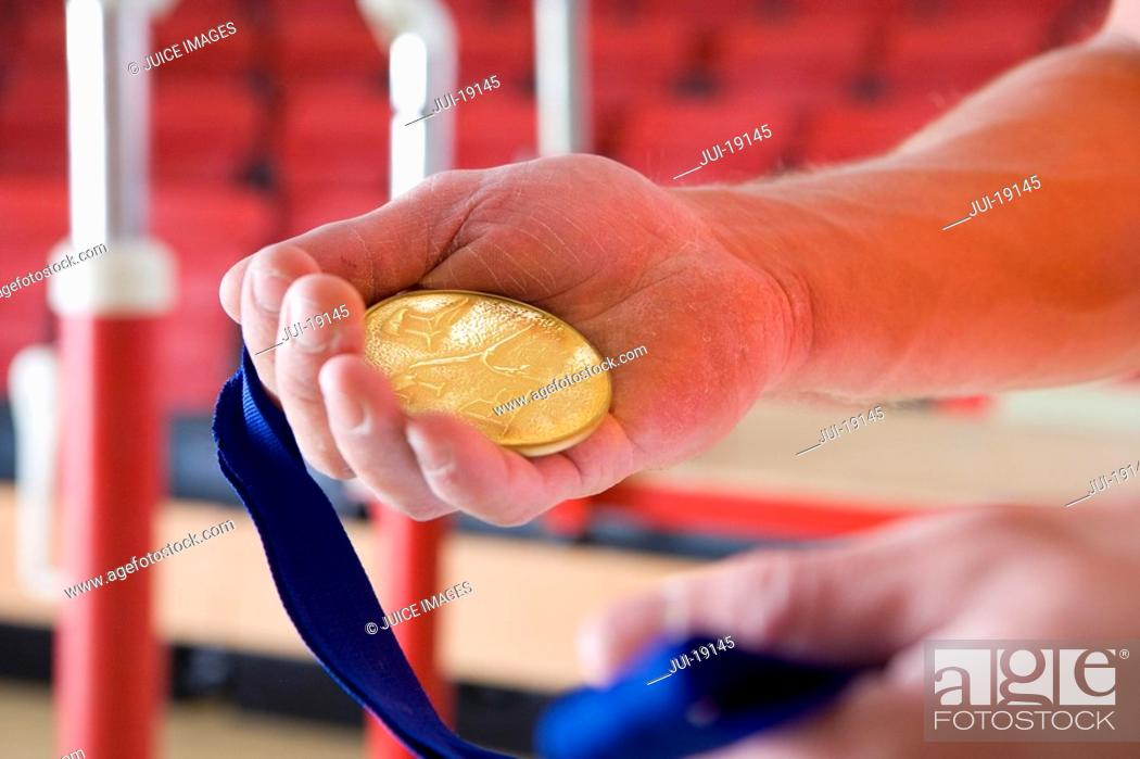 Stock Photo: Male gymnast holding gold medal, close-up of hands.