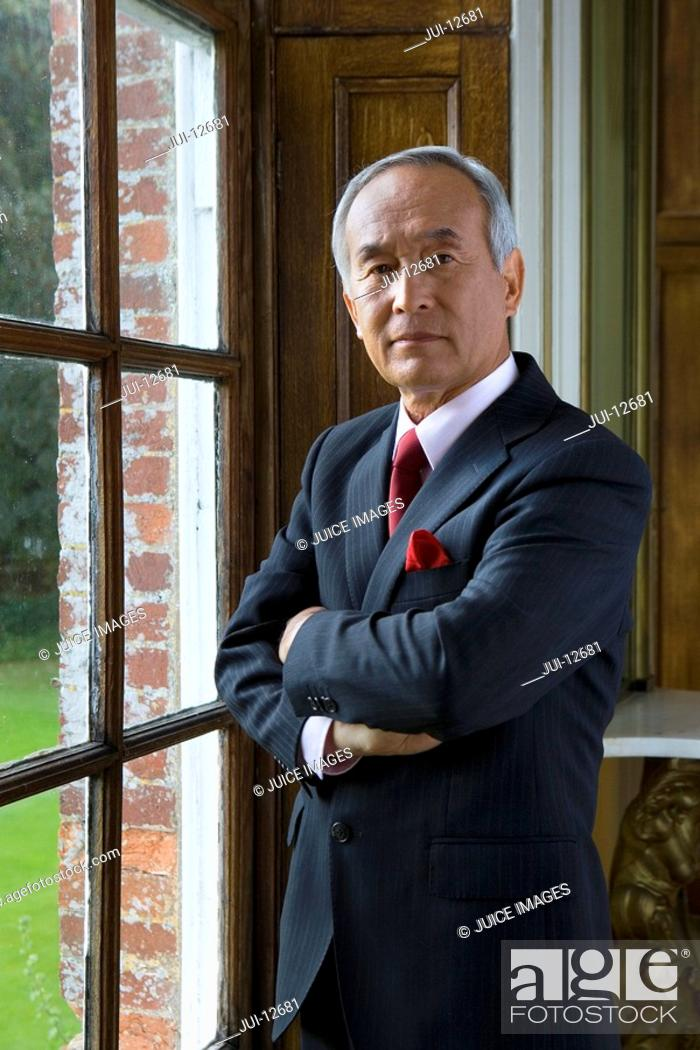 Stock Photo: Mature businessman by window, arms crossed, portrait.