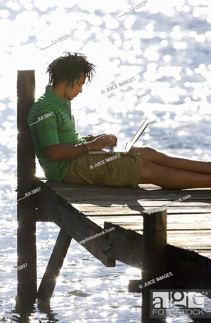 Stock Photo: Solitary young man sitting on jetty beside lake, using laptop, profile.
