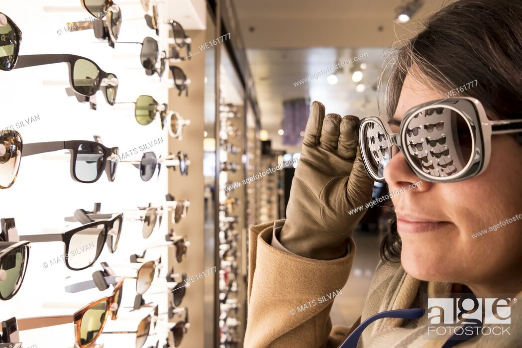Imagen: Woman Testing Sunglasses in Retail Store.